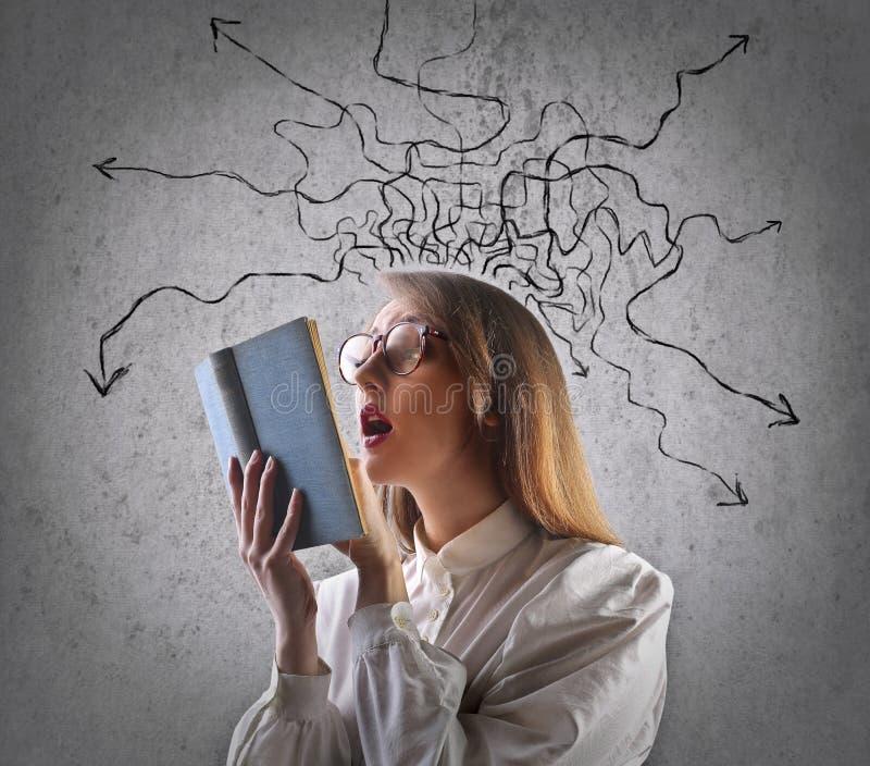 Ung kvinna med långt hårsammanträde i läsning för fönsterplats arkivfoton