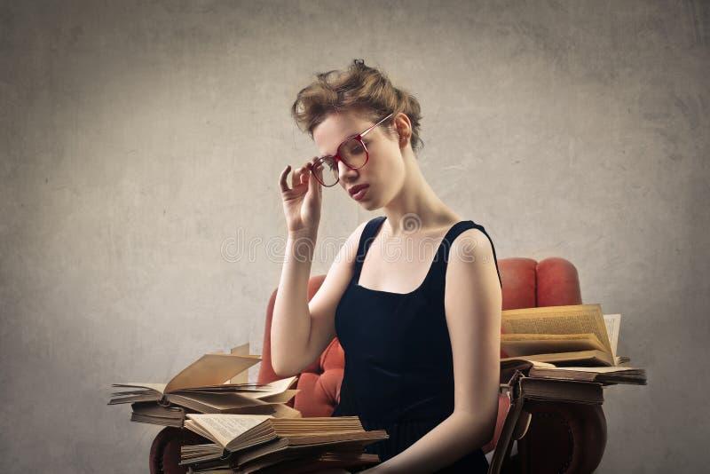 Ung kvinna med långt hårsammanträde i läsning för fönsterplats royaltyfria bilder