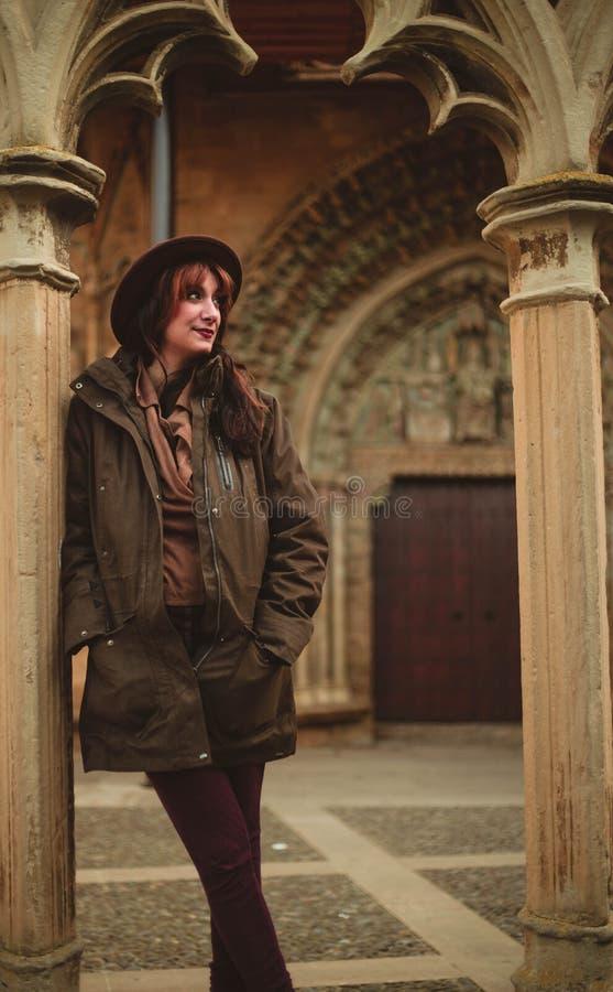 Ung kvinna med laget och hatten som lutar på kolonnen i en domkyrka i Olite Navarra Spanien royaltyfri foto