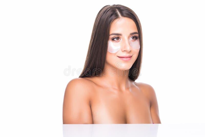 Ung kvinna med lappar under ögonen av mörka cirklar och skrynklor som att bry sig för hennes framsida som isoleras på vit bakgrun arkivfoton