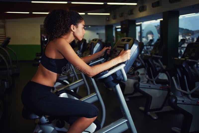 Ung kvinna med lockigt afro hår som övar på den cardio snurrcykeln arkivbild