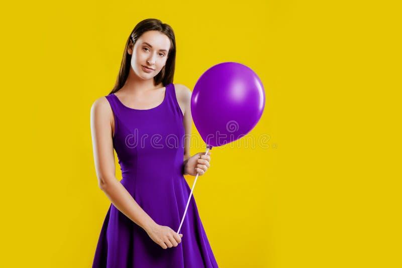 Ung kvinna med luftballongen över gul bakgrund royaltyfria bilder