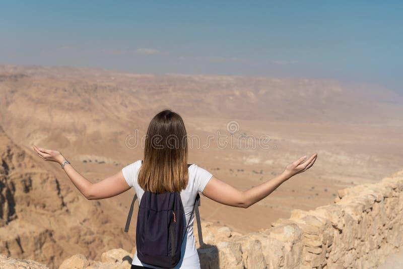 Ung kvinna med lyftta armar se panoraman över öknen i Israel royaltyfria bilder