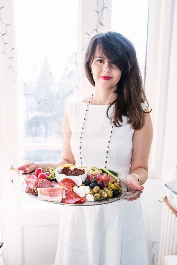 Ung kvinna med matuppläggningsfatet royaltyfri foto