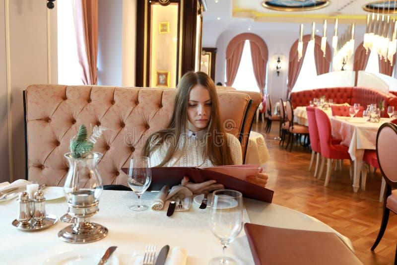 Ung kvinna med menyboken arkivbilder
