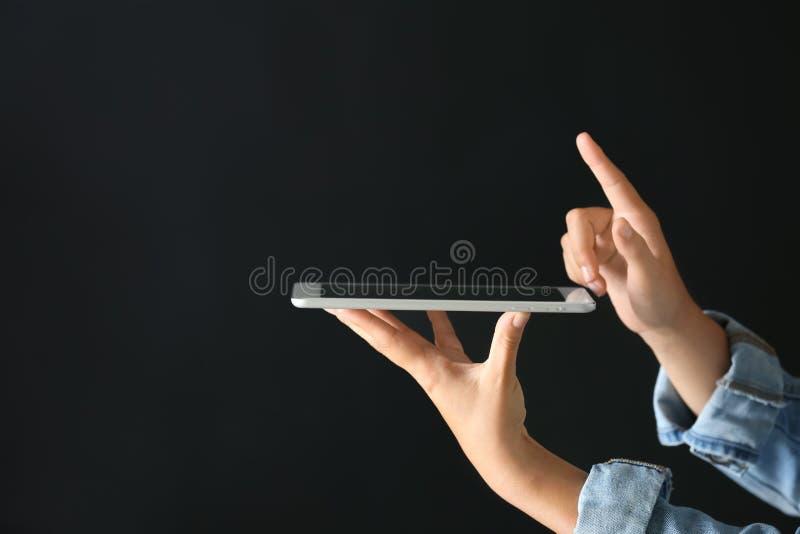 Ung kvinna med minnestavlaPC genom att använda den faktiska skärmen på mörk bakgrund royaltyfri foto