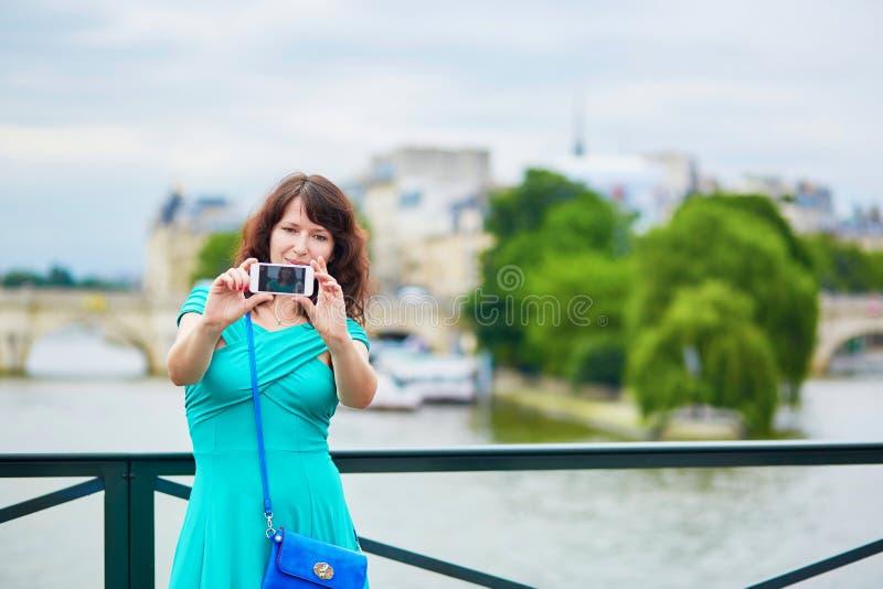 Ung kvinna med mobiltelefonen i Paris fotografering för bildbyråer