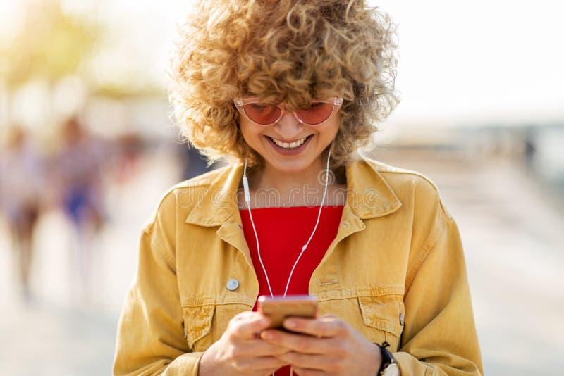 Ung kvinna med mobiltelefonen i staden arkivbilder