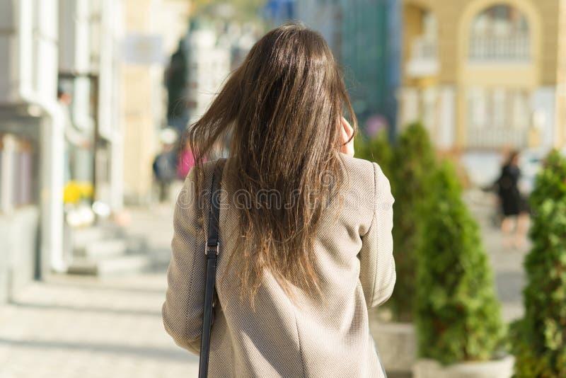 Ung kvinna med mobiltelefonen som går i den soliga stadsgatan, flicka som bär det varma laget, sikt från baksidan, guld- timme royaltyfri bild