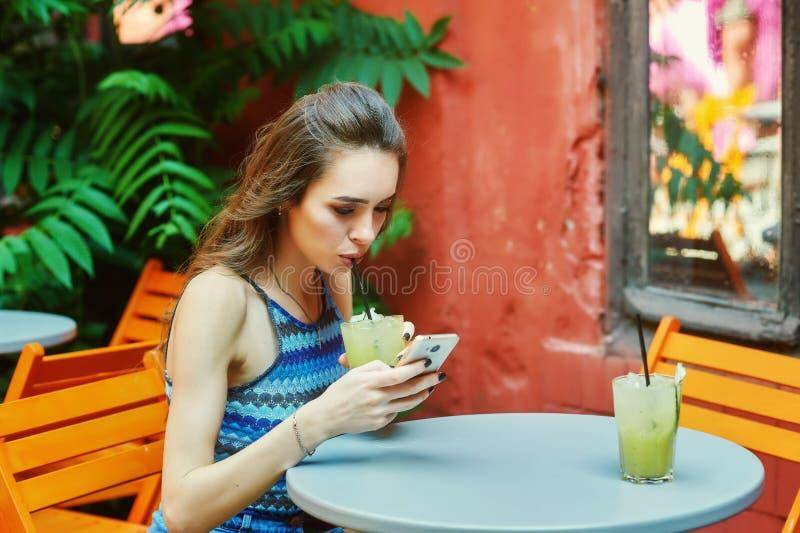Ung kvinna med mobiltelefonsammanträde i kafé royaltyfri foto