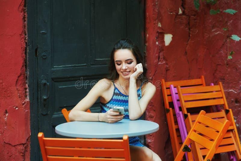 Ung kvinna med mobiltelefonsammanträde i kafé royaltyfria foton