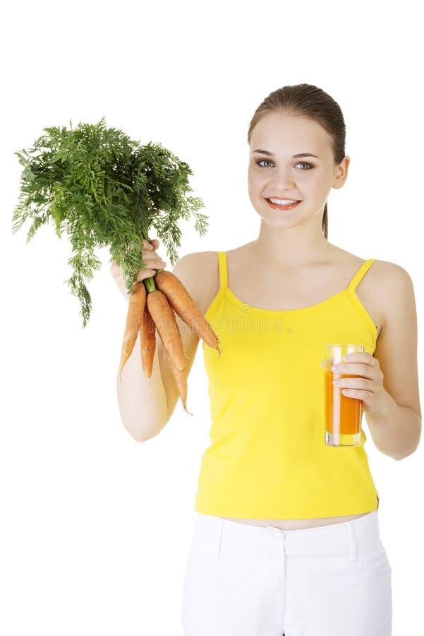 Ung kvinna med morotfruktsaften arkivfoto