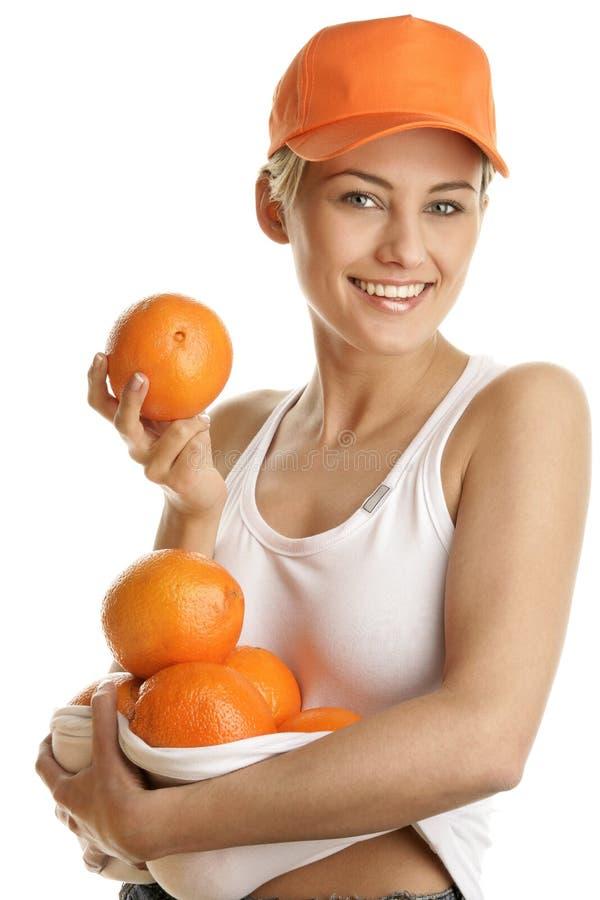 Ung kvinna med nya apelsiner arkivfoto