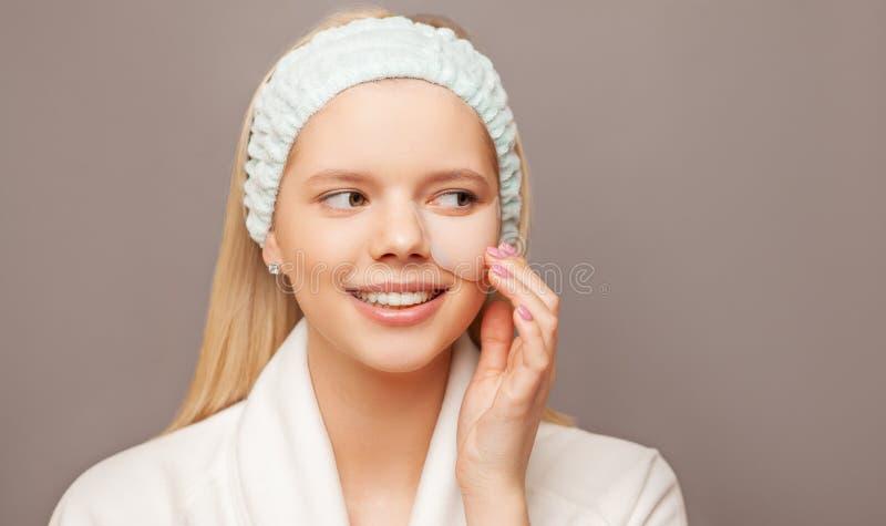 Ung kvinna med nya sunda hud och hår genom att använda lappar och att le Cosmetology, skönhet och brunnsort arkivfoto