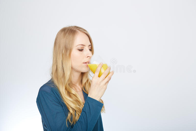 Ung kvinna med orange fruktsaft som isoleras på vit arkivbilder
