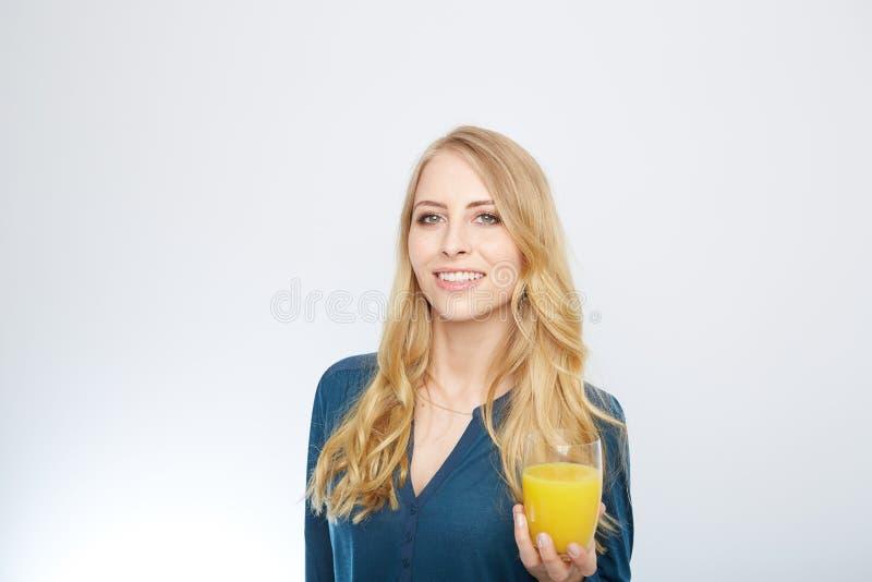 Ung kvinna med orange fruktsaft som isoleras på vit arkivfoton