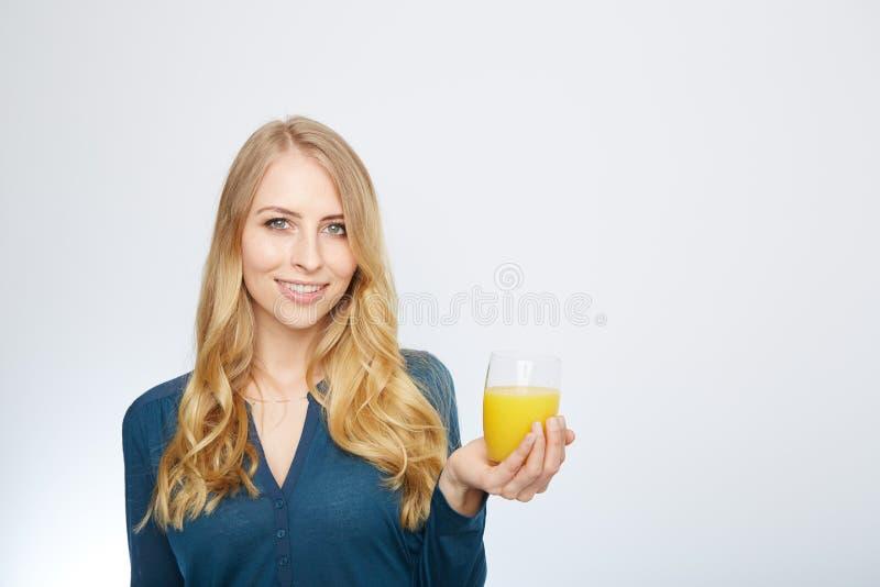 Ung kvinna med orange fruktsaft som isoleras på vit royaltyfri bild