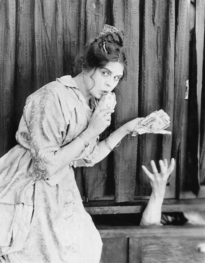 Ung kvinna med pengar i hennes händer som ger den till någon (alla visade personer inte är längre uppehälle, och inget gods finns arkivbilder