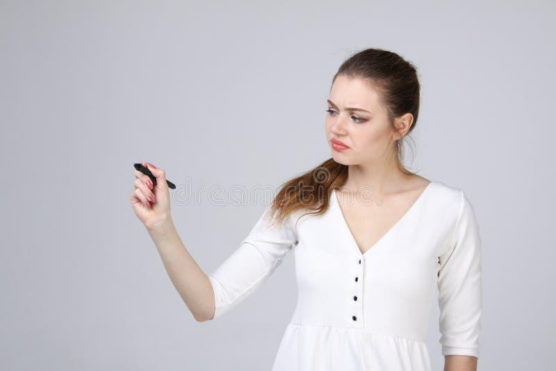 Ung kvinna med pennan på grå bakgrund arkivfoto