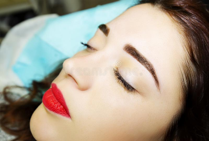 Ung kvinna med permanent ögonbrynmakeup, closeup arkivbild