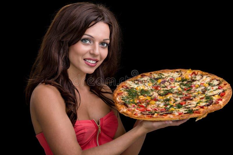 Ung kvinna med pizza mot svart bakgrund royaltyfri fotografi