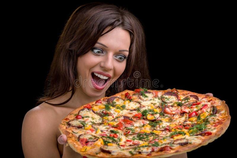 Ung kvinna med pizza mot svart bakgrund fotografering för bildbyråer