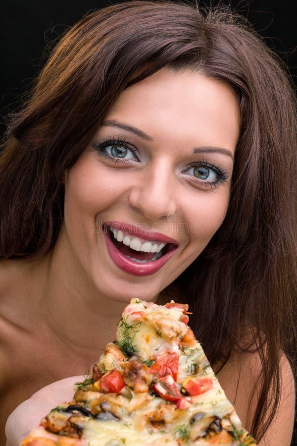 Ung kvinna med pizza mot svart bakgrund arkivbild