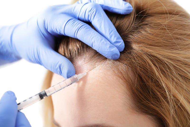 Ung kvinna med problemet för hårförlust som mottar injektionen royaltyfri bild