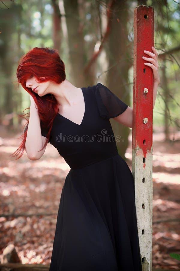 Ung kvinna med rött hår i elegant aftonklänning i skogen royaltyfri foto