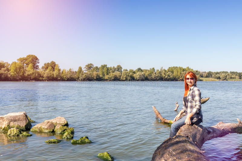 Ung kvinna med rött hår på floden arkivbilder