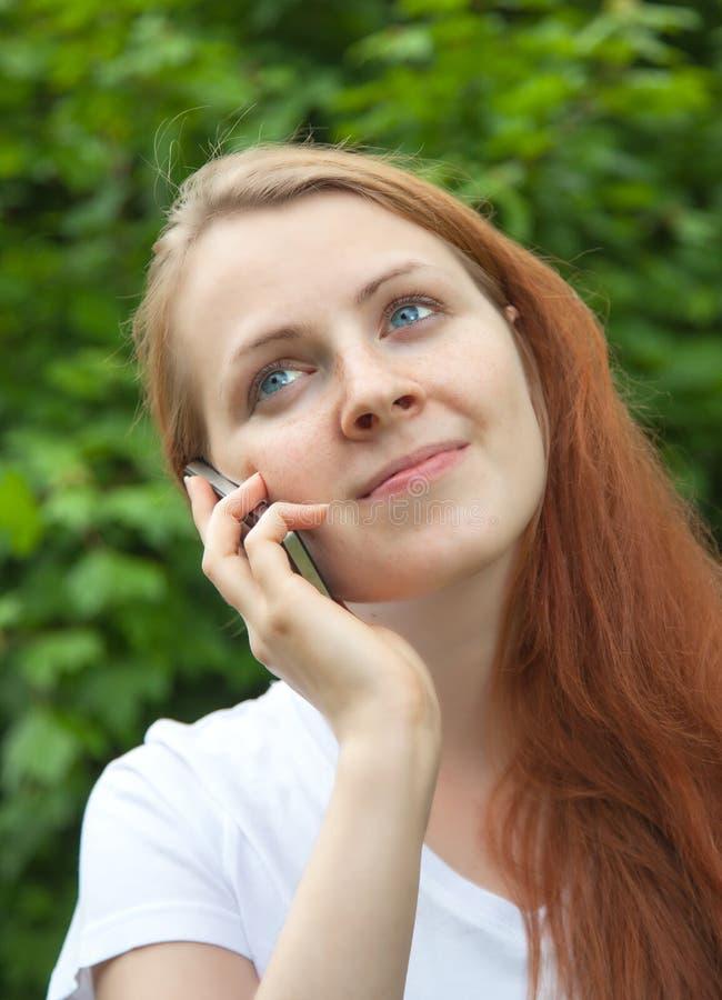 Ung kvinna med rött hår som lyssnar till telefonen i en parkera royaltyfri foto