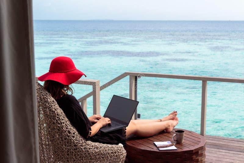 Ung kvinna med rött hattarbete på en dator i en tropisk destination arkivfoton