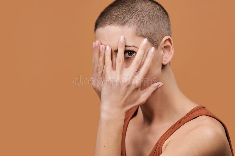 Ung kvinna med rakat täcka för huvud hennes framsida med båda händer och att kika till och med fingrar Kvinna med skrämt uttryck royaltyfri foto