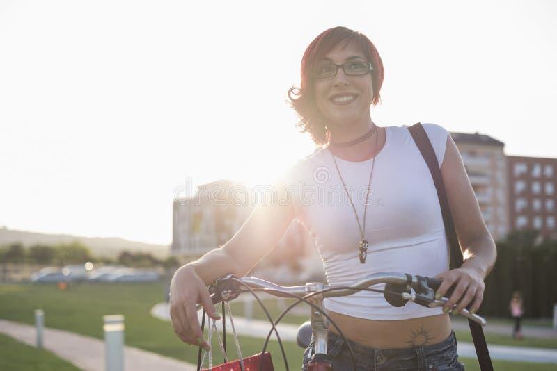 Ung kvinna med rittcykeln i staden Posera med solnedgångbackl arkivbild