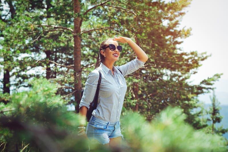Ung kvinna med ryggsäckanseende på kanten för klippa` s och att se till en himmel arkivbilder