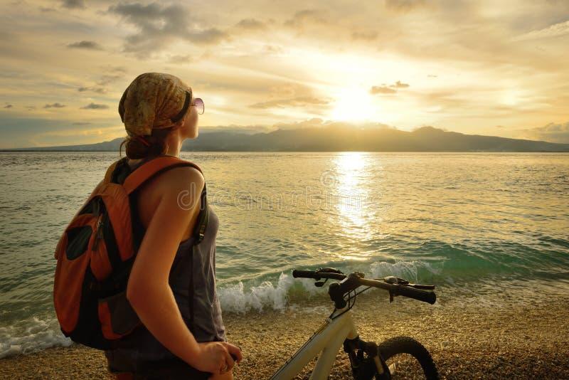 Ung kvinna med ryggsäckanseende på kusten nära hans cykel fotografering för bildbyråer