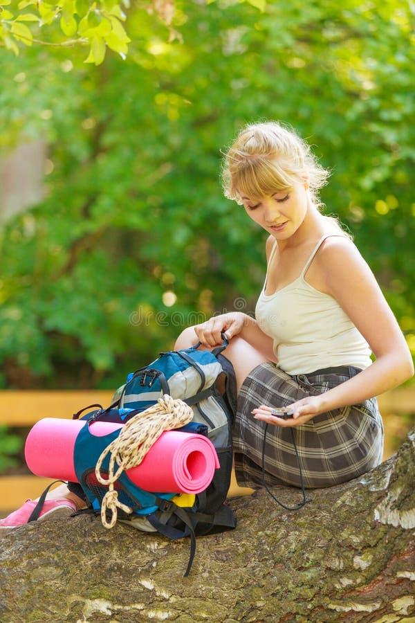 Ung kvinna med ryggsäcken som fotvandrar i skogslinga arkivbilder