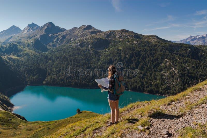 Ung kvinna med ryggsäcken som läser en översikt i de schweiziska fjällängarna Sjöritom som bakgrund arkivfoto