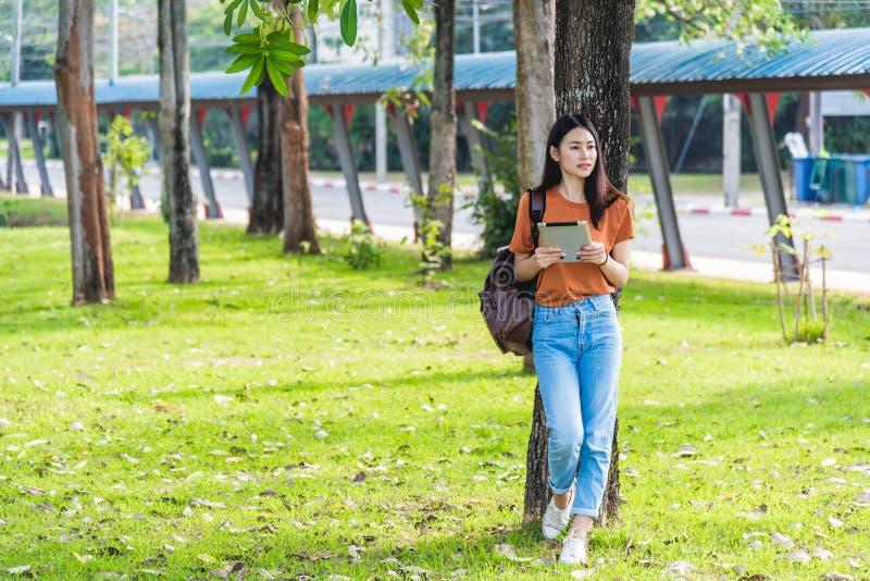 Ung kvinna med ryggsäckhållanteckningsboken royaltyfria foton