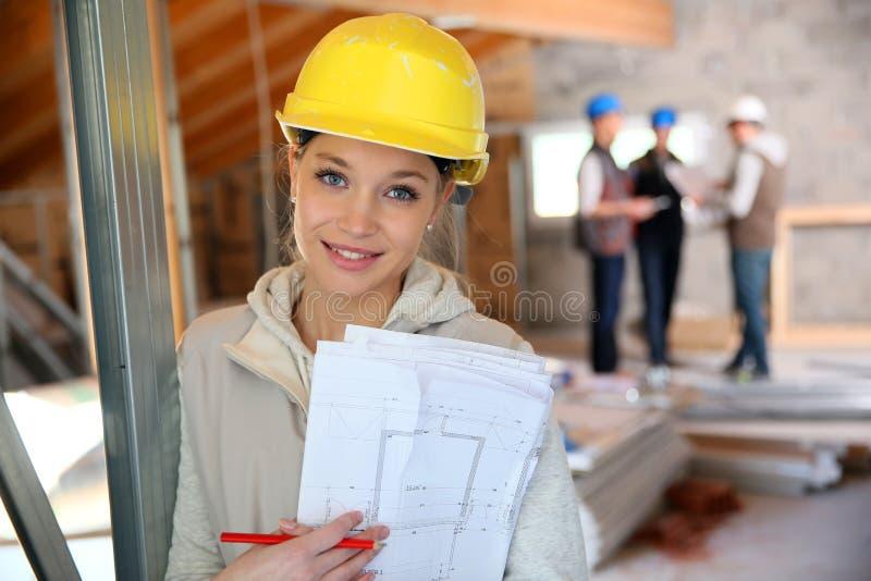 Ung kvinna med säkerhetshjälmen under konstruktion arkivfoton