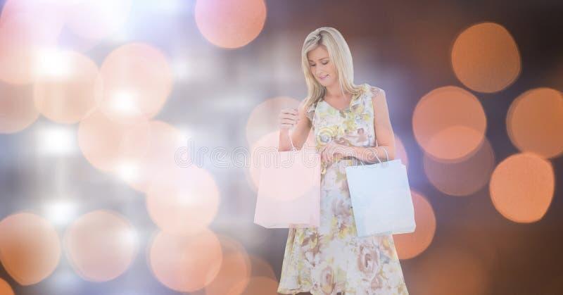 Ung kvinna med shoppingpåsar över bokeh arkivbild