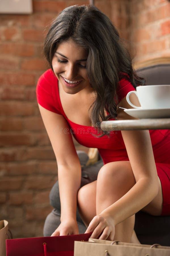 Ung kvinna med shoppingpåsar i ett kafé royaltyfria bilder