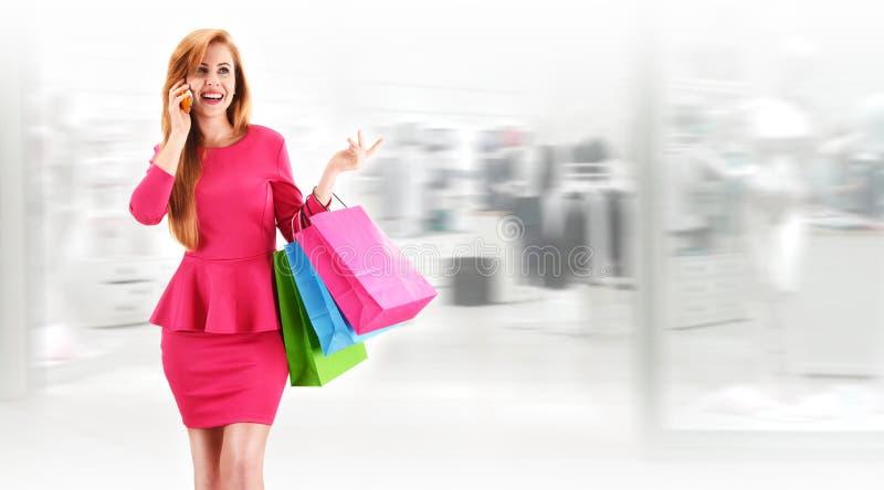 Ung kvinna med shoppingpåsar i kommersiell mitt royaltyfria bilder