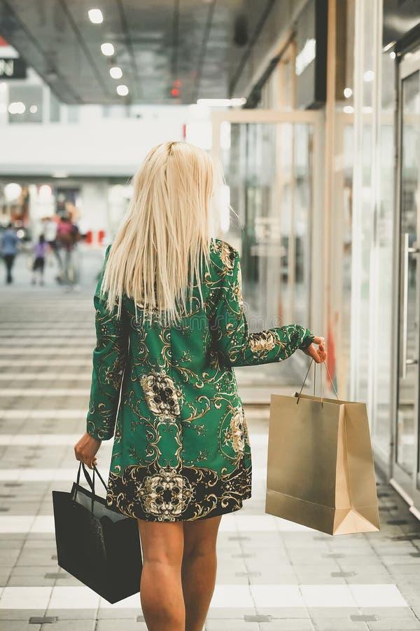 Ung kvinna med shoppingpåsar som tycker om i shopping royaltyfri bild