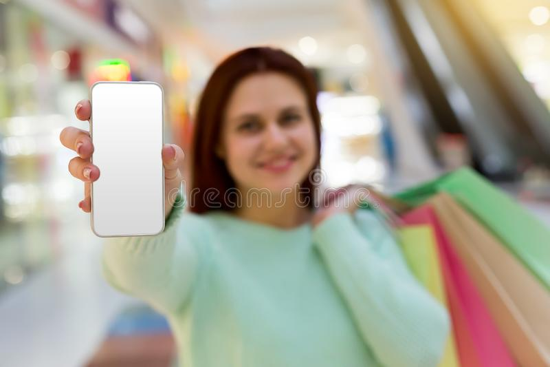 Ung kvinna med shoppingpåsar som visar telefonens skärm direkt till kameran royaltyfria bilder
