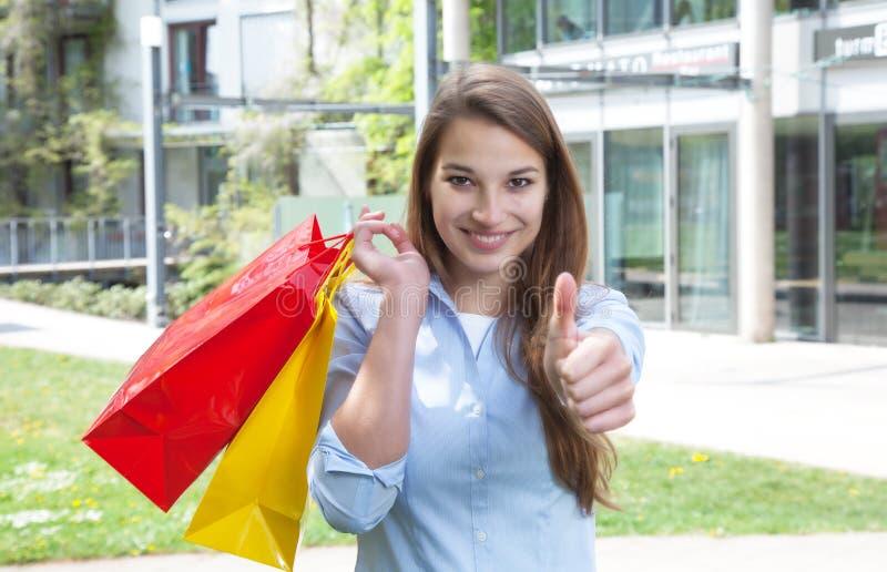 Ung kvinna med shoppingpåsar som visar upp tummen arkivfoton