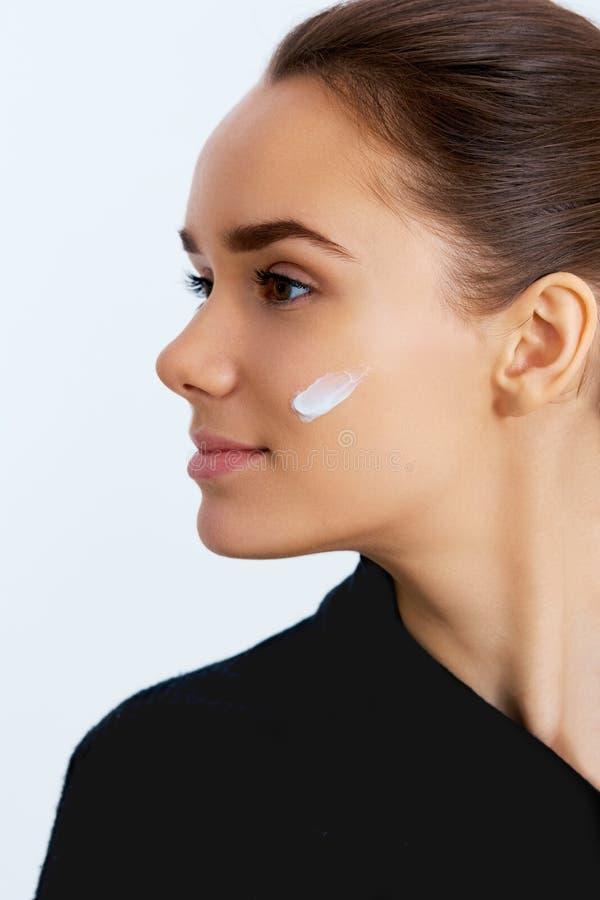 Ung kvinna med skönhetsmedelkräm på en ren ny framsida Härlig modell som applicerar kosmetisk kräm- behandling på hennes framsida royaltyfri fotografi