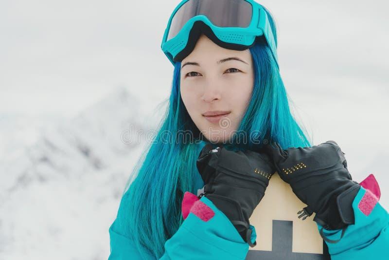 Ung kvinna med snowboarden i vinter arkivbild