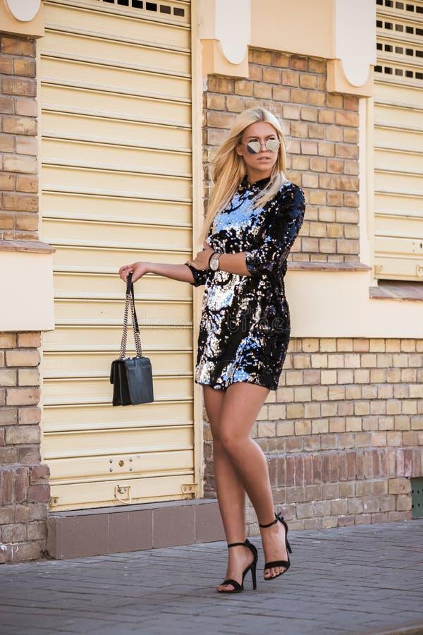 Ung kvinna med solglasögon som går på gatan royaltyfria bilder