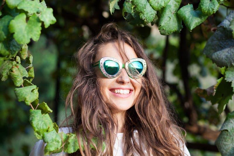 Ung kvinna med solglasögon som står under sidor royaltyfria foton